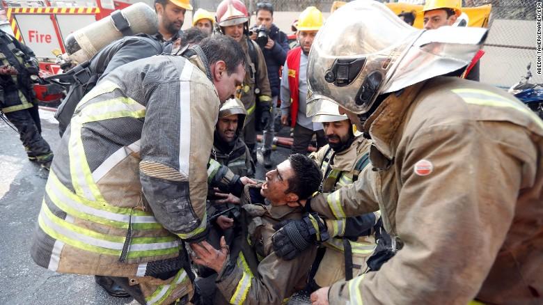Bomberos iraníes consuelan a un compañero, tras el colapso del edificio.