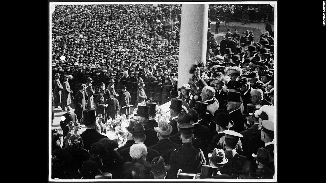 El presidente Warren G. Harding saluda a la multitud desde el pórtico del Capitolio de Estados Unidos en 1921. Fue la primera toma de posesión en la que se usó un automóvil para transportar al mandatario hasta el Capitolio.