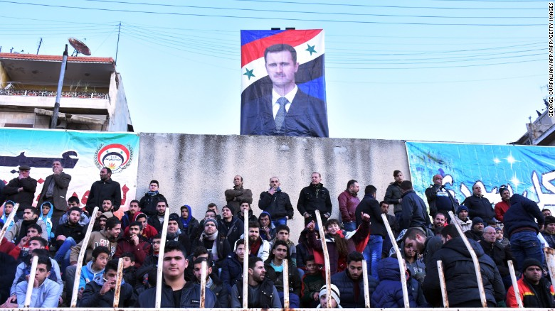 La imagen de Al Assad en lo alto de la tribuna.