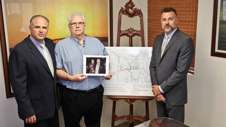 Antonio Caballero (c) con sus abogados y sosteniendo una foto de sus padres.