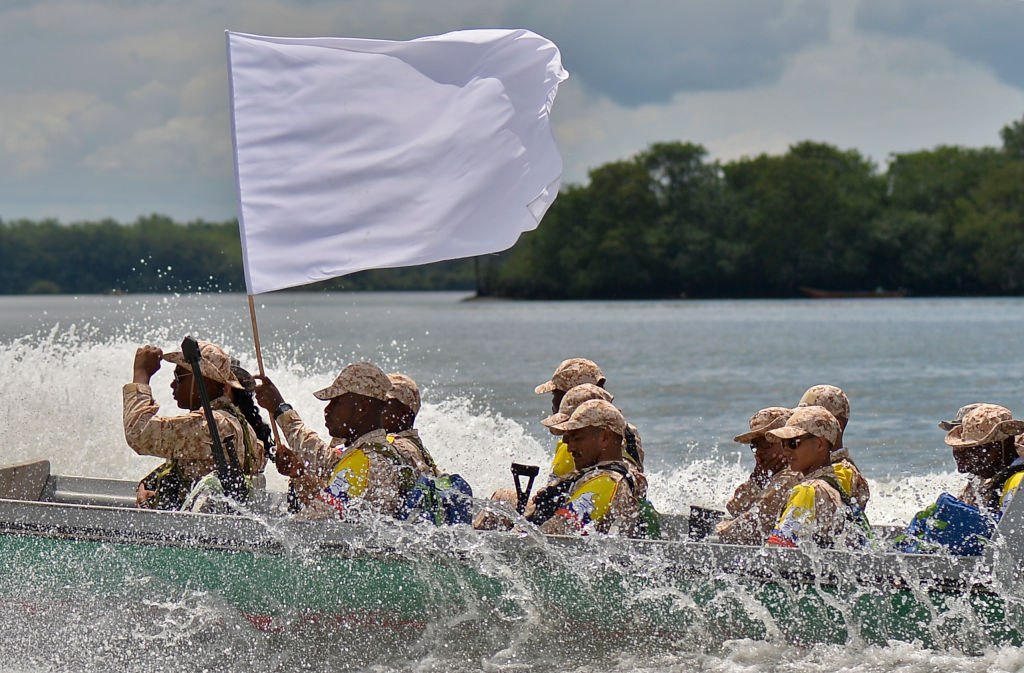 Imagen de los miembros de la guerrilla de las FARC llevan una bandera blanca al llegar al puerto de Buenaventura el 4 de febrero de 2017 durante el proceso de movilización hacia las Zonas Veredales Transitorias de Normalización. (Crédito: LUIS ROBAYO/AFP/Getty Images)