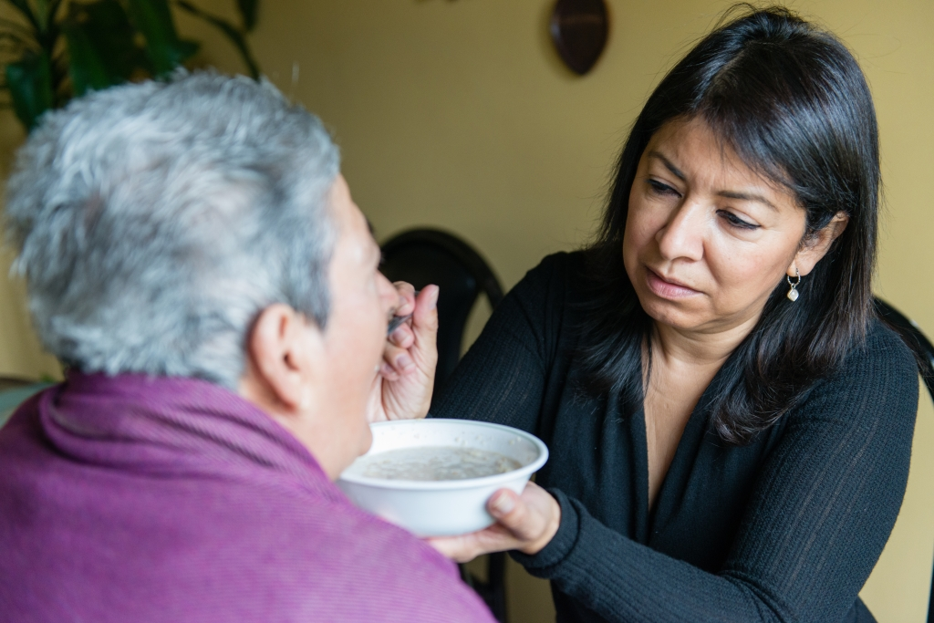 """Tania Yanes feeds oatmeal to her mother, Blanca Rosa Rivera, on Sunday, November 27, 2016. """"My mom is 100 percent dependent on us."""" says Yanes. (Heidi de Marco/KHN)"""