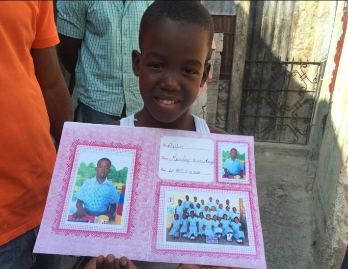 Monley Elysee sostiene una foto suya en el colegio en el que estudia, en Puerto Príncipe.