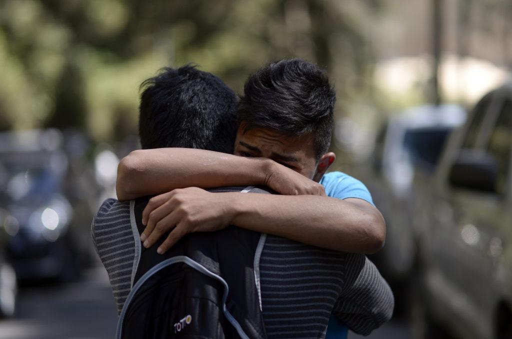 Familiares de los menores lloran a las afueras del centro de rehabilitación de Guatemala esperando noticias tras el incendio.