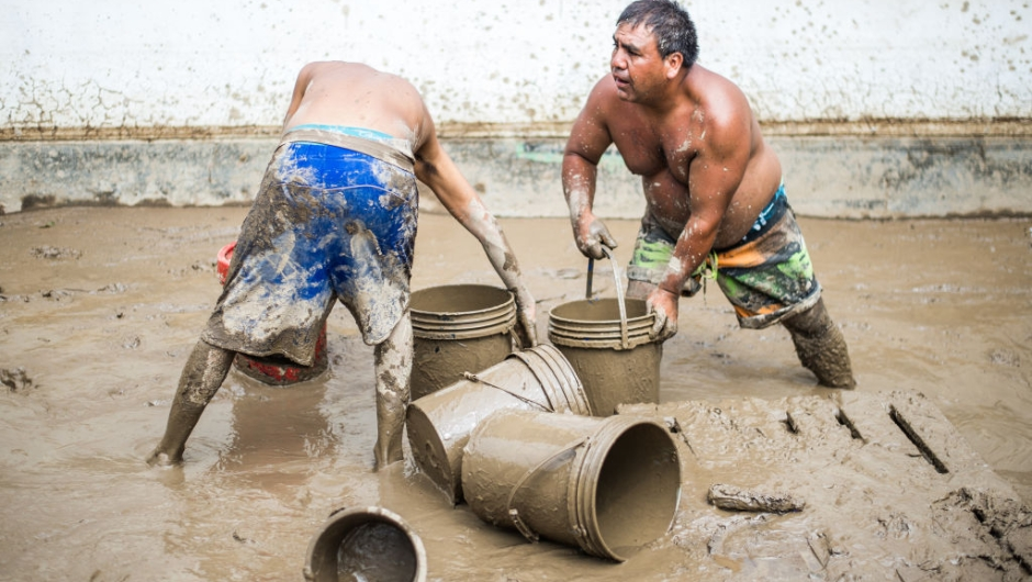 Residents of a populous district of Lima remove from their house mud, debris and water left by a flash flood, on March 19, 2017. El Nino-fuelled flash floods and landslides hit parts of Lima, where most of the water distribution systems have collapsed due to unusual heavy seasonal downpours and people are facing drinking water shortages. / AFP PHOTO / Ernesto BENAVIDES (Photo credit should read ERNESTO BENAVIDES/AFP/Getty Images)