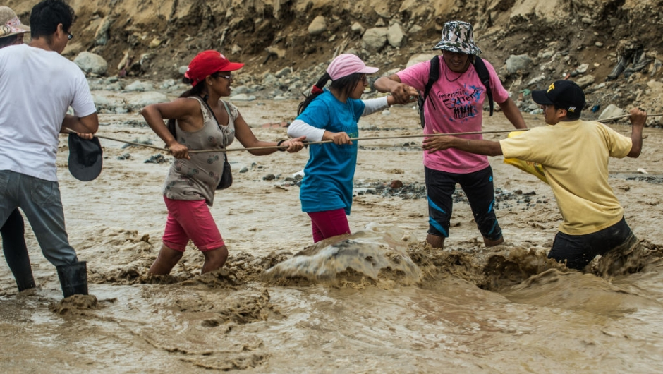Local residents try to cross a flash flood in Huachipa district, on the east side of Lima, on March 19, 2017. El Nino-fuelled flash floods and landslides hit parts of Lima, where most of the water distribution systems have collapsed due to unusual heavy seasonal downpours and people are facing drinking water shortages. / AFP PHOTO / ERNESTO BENAVIDES (Photo credit should read ERNESTO BENAVIDES/AFP/Getty Images)