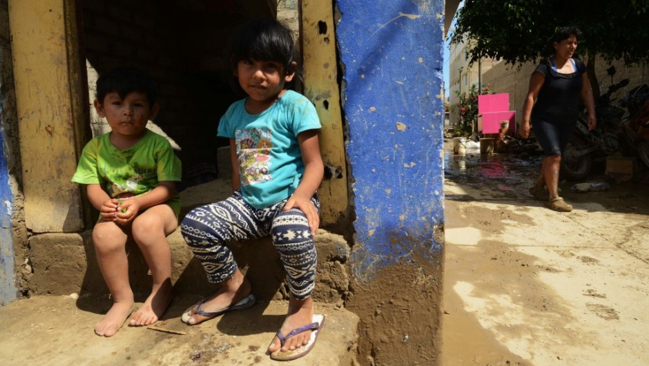 Children sit on their doorstep in the town of Huarmey, 300 kilometres north of Lima, where the ground was covered on March 19, 2017 with several centimetres of mud and silt after a flash flood hit the evening before. The El Nino climate phenomenon is causing muddy rivers to overflow along the entire Peruvian coast, isolating communities and neighbourhoods. Thousands have been affected since January, and 72 people have died. Most cities face water shortages as water lines have been compromised by mud and debris. / AFP PHOTO / CRIS BOURONCLE (Photo credit should read CRIS BOURONCLE/AFP/Getty Images)