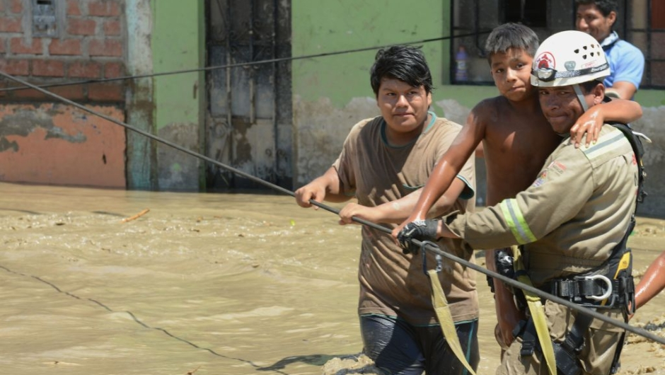 Rescue workers help local residents of the town of Huarmey, 300 kilometres north of Lima, wade through muddy water in the street on March 19, 2017 after a flash flood hit the evening before. The El Nino climate phenomenon is causing muddy rivers to overflow along the entire Peruvian coast, isolating communities and neighbourhoods. Thousands have been affected since January, and 72 people have died. Most cities face water shortages as water lines have been compromised by mud and debris. / AFP PHOTO / CRIS BOURONCLE (Photo credit should read CRIS BOURONCLE/AFP/Getty Images)