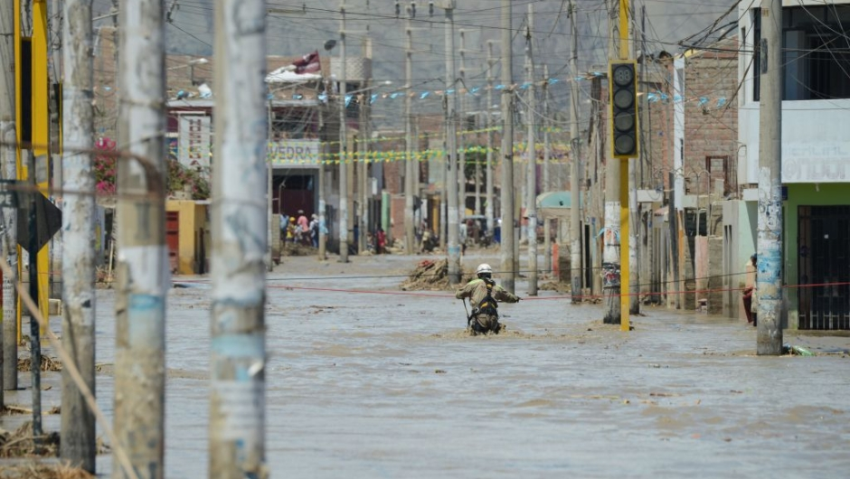 A rescue workers waits to help local residents of the town of Huarmey, 300 kilometres north of Lima, wade through muddy water on the street on March 19, 2017 after a flash flood hit the evening before. The El Nino climate phenomenon is causing muddy rivers to overflow along the entire Peruvian coast, isolating communities and neighbourhoods. Thousands have been affected since January, and 72 people have died. Most cities face water shortages as water lines have been compromised by mud and debris. / AFP PHOTO / CRIS BOURONCLE (Photo credit should read CRIS BOURONCLE/AFP/Getty Images)