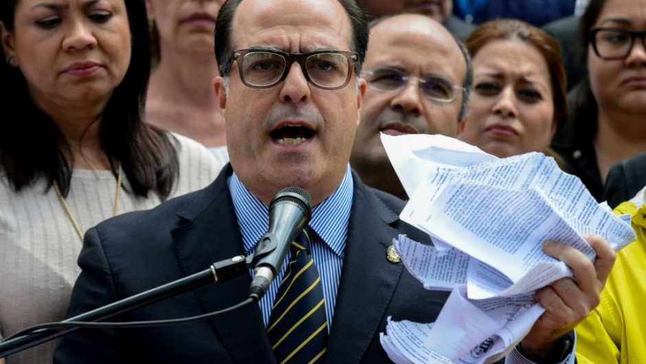 """The president of Venezuela's National Assembly Julio Borges, holds a tore copy of a sentence from Venezuela's Supreme Court granting itself legislative powers, as he speaks during a press conference in Caracas on March 30, 2017. Venezuela's Supreme Court took over legislative powers Thursday from the opposition-majority National Assembly, whose speaker accused leftist President Nicolas Maduro of staging a """"coup."""" / AFP PHOTO / FEDERICO PARRA (Photo credit should read FEDERICO PARRA/AFP/Getty Images)"""