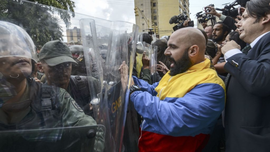 """OPSHOT - CORRECTION - Venezuelan opposition deputy Marco Bozo (C) scuffles with National Guard personnel in riot gear during a protest in front of the Supreme Court in Caracas on March 30, 2017. Venezuela's Supreme Court took over legislative powers Thursday from the opposition-majority National Assembly, whose speaker accused leftist President Nicolas Maduro of staging a """"coup."""" / AFP PHOTO / JUAN BARRETO / The erroneous mention[s] appearing in the metadata of this photo by JUAN BARRETO has been modified in AFP systems in the following manner: [Marco Bozo] instead of [Carlos Bozo]. Please immediately remove the erroneous mention[s] from all your online services and delete it (them) from your servers. If you have been authorized by AFP to distribute it (them) to third parties, please ensure that the same actions are carried out by them. Failure to promptly comply with these instructions will entail liability on your part for any continued or post notification usage. Therefore we thank you very much for all your attention and prompt action. We are sorry for the inconvenience this notification may cause and remain at your disposal for any further information you may require. (Photo credit should read JUAN BARRETO/AFP/Getty Images)"""