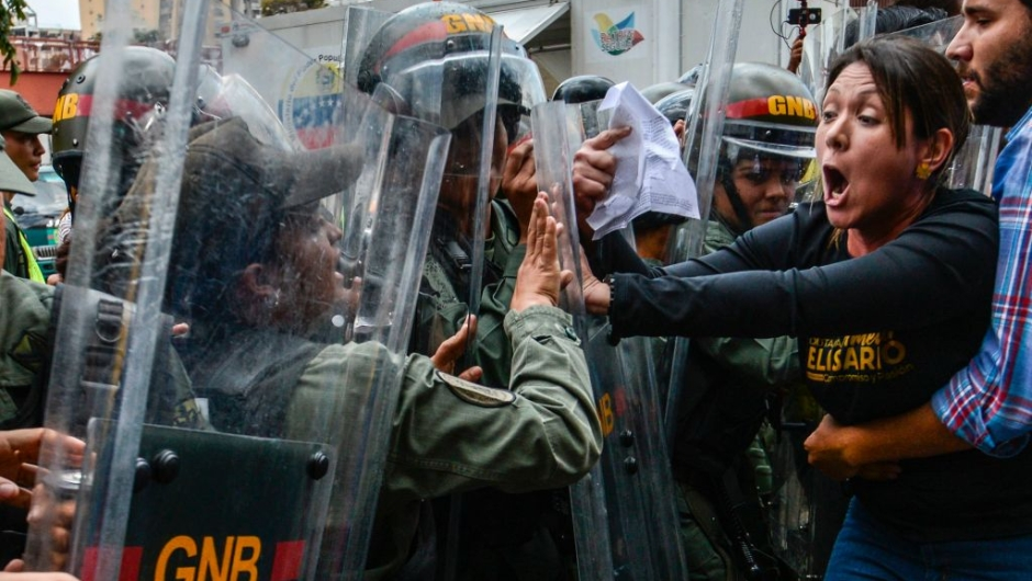 """TOPSHOT - Venezuelan opposition deputy Amelia Belisario (2nd-R) scuffles with National Guard personnel in riot gear during a protest in front of the Supreme Court in Caracas on March 30, 2017. Venezuela's Supreme Court took over legislative powers Thursday from the opposition-majority National Assembly, whose speaker accused leftist President Nicolas Maduro of staging a """"coup."""" / AFP PHOTO / JUAN BARRETO (Photo credit should read JUAN BARRETO/AFP/Getty Images)"""