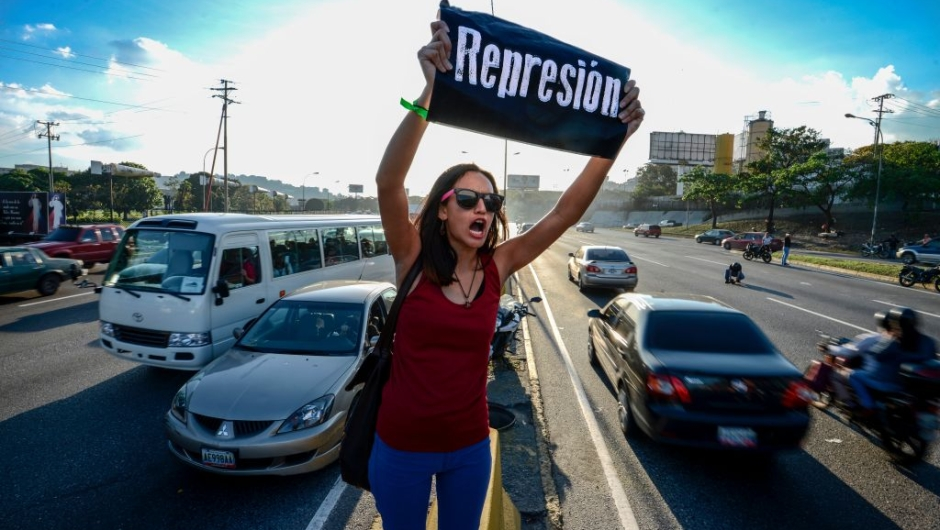 """A student shouts slogans against Venezuelan President Nicola Maduro during a protest on the main highway in Caracas on March 30, 2017. Venezuela's Supreme Court took over legislative powers Wednesday from the opposition-majority National Assembly, whose speaker accused leftist President Nicolas Maduro of staging a """"coup."""" / AFP PHOTO / Juan BARRETO (Photo credit should read JUAN BARRETO/AFP/Getty Images)"""