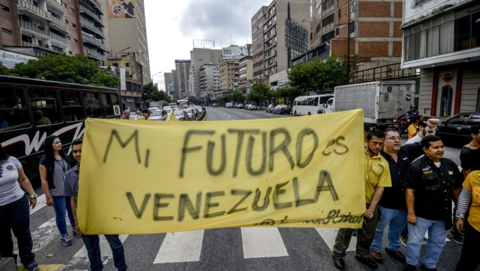 """Venezuelan opposition activists march along a street of Caracas on March 31, 2017 chanting slogans against the government of President Nicolas Maduro and deploying a banner that reads """"My Future Is Venezuela"""". Venezuela's Supreme Court took over legislative powers Thursday from the opposition-majority National Assembly, whose speaker accused leftist President Nicolas Maduro of staging a """"coup."""" / AFP PHOTO / Juan Barreto (Photo credit should read JUAN BARRETO/AFP/Getty Images)"""
