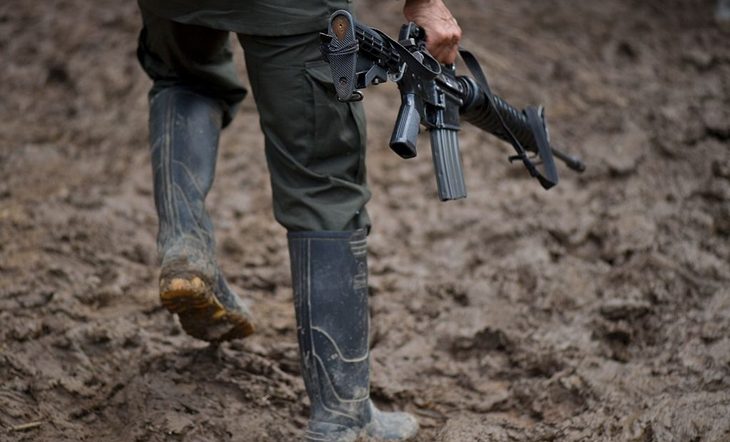 "TOPSHOT - A member of the Revolutionary Armed Forces of Colombia (FARC) guerrilla carries his rifle at the ""Alfonso Artiaga"" Front 29 FARC encampment in a rural area of Policarpa, department of Narino in southwestern Colombia, on January 16, 2017. The UN is overseeing the FARC's disarmament as part of a peace deal the leftist guerrillas signed with the government to end a more than five-decade conflict. The FARC's 5,700 fighters are now in camps waiting to be transferred to UN-monitored ZVTN transitional zones where they will demobilize and begin their path to civilian life and legality over a period of six months. But the delay in setting up the camps has hindered their transfer to these areas. / AFP / LUIS ROBAYO (Photo credit should read LUIS ROBAYO/AFP/Getty Images)"