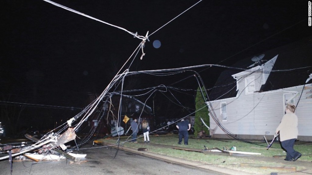 Personas caminan entre cables caídos después de que una tormenta pasara por Naplate, el martes.