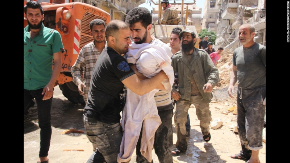 The father of a three-month old girl whose body was pulled out of the rubble weeps as he approaches the rescuer to carry her following a barrel bomb strike said to be launched by Syrian government forces on May 26, 2014 in the northern Syrian city of Aleppo in which serveral people were reported killed or wounded. Syrian President Bashar al-Assad, facing two little-known challengers in a June 3 presidential election, is widely expected to clinch a third seven-year term despite Syria's civil war, which has killed more than 160,000 people. AFP PHOTO / BARAA AL-HALABI (Photo credit should read BARAA AL-HALABI/AFP/Getty Images)