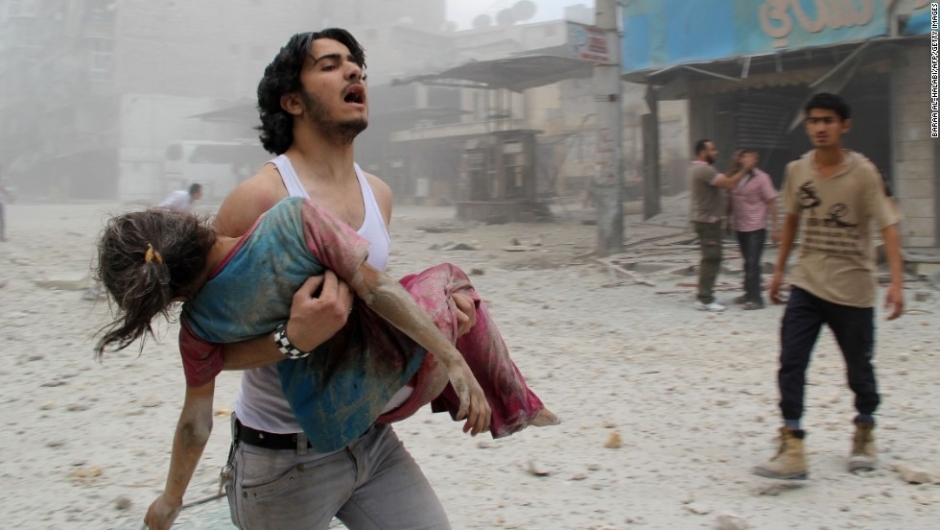 TOPSHOTS A man carries a young girl who was injured in a reported barrel-bomb attack by government forces on June 3, 2014 in Kallaseh district in the northern city of Aleppo. Some 2,000 civilians, including more than 500 children, have been killed in regime air strikes on rebel-held areas of Aleppo since January, many of them in barrel bomb attacks. AFP PHOTO / BARAA AL-HALABIBARAA AL-HALABI/AFP/Getty Images
