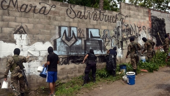 Police officers and soldiers paint over graffiti associated with the Mara Salvatrucha gang in Quezaltepeque, a town 15 km from San Salvador, in an operation to take back gang-controlled neighborhoods, on June 7, 2016. The Salvatrucha (MS-13) and 18th Street gangs are the main cause of the escalation of violence plaguing El Salvador, where an estimated 60,000 people belong to gangs, 15,000 of them in prison. / AFP / Marvin RECINOS (Photo credit should read MARVIN RECINOS/AFP/Getty Images)