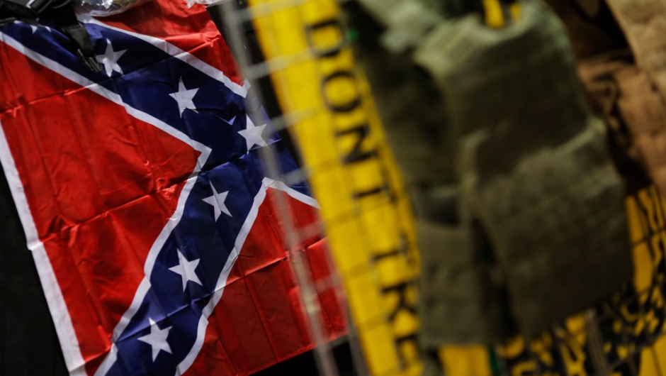 A Confederate battle flag and a Gadsden flag are seen with body armor on display at a National Rifle Association outdoor sports trade show on February 10, 2017 in Harrisburg, Pennsylvania. The Great American Outdoor Show, a nine day event celebrating hunting, fishing and outdoor traditions, features over 1,000 exhibitors ranging from shooting manufacturers to outfitters to fishing boats and RVs, and archery to art. / AFP / DOMINICK REUTER (Photo credit should read DOMINICK REUTER/AFP/Getty Images)