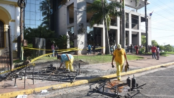 Town hall civil servants clean burnt fences outside the Congress, set on fire on the eve by demonstrators protesting against the approval of a constitutional amendment for presidential reelection in Asuncion on April 1, 2017. Paraguayan senators approved a contested law allowing President Horacio Cartes to seek reelection in 2018, prompting furious protesters to break into the legislature, ransacking lawmakers' offices and starting fires. / AFP PHOTO / NORBERTO DUARTE (Photo credit should read NORBERTO DUARTE/AFP/Getty Images)