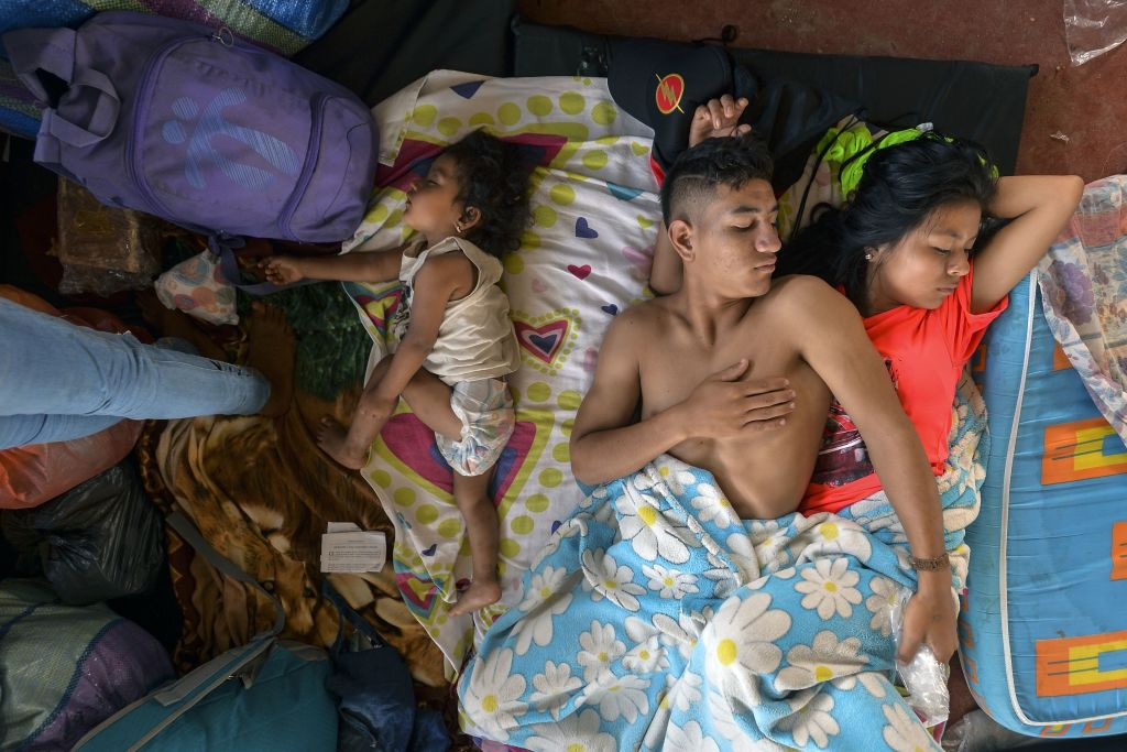 TOPSHOT - A family rests at a shelter in Mocoa, Putumayo department, southern Colombia on April 3, 2017. Residents of Mocoa were Monday desperately searching for loved ones missing since devastating mudslides slammed into the remote Colombian town, as the death toll soared to over 250, including 43 children. / AFP PHOTO / LUIS ROBAYO (Photo credit should read LUIS ROBAYO/AFP/Getty Images)
