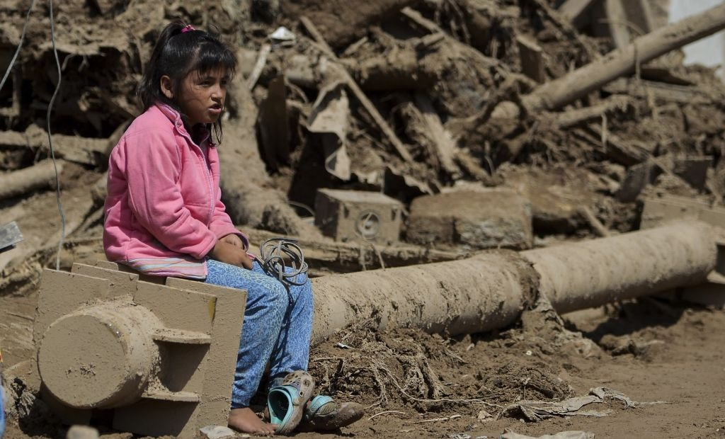 A girl sits amid the debris left by mudslides caused by heavy rains in Mocoa, Putumayo department, southern Colombia on April 4, 2017. The Colombian government on Monday declared a state of economic emergency in the town of Mocoa in southern Colombia, after mudslides left more than 270 people dead, including 43 children. / AFP PHOTO / LUIS ROBAYO (Photo credit should read LUIS ROBAYO/AFP/Getty Images)