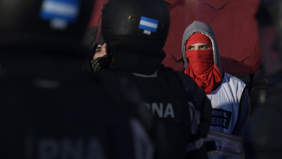 TOPSHOT - A masked protester stands next to members of Prefectura Naval Argentina who guard the entrance of Pueyrredon bridge blocked by demonstrators in Avellaneda, Buenos Aires on April 6, 2017, during a 24 hours general strike. A 24 hours general strike was called by worker's unions demanding to President Mauricio Macri's government to take measures against inflation and keep campaign promises. / AFP PHOTO / JUAN MABROMATA (Photo credit should read JUAN MABROMATA/AFP/Getty Images)