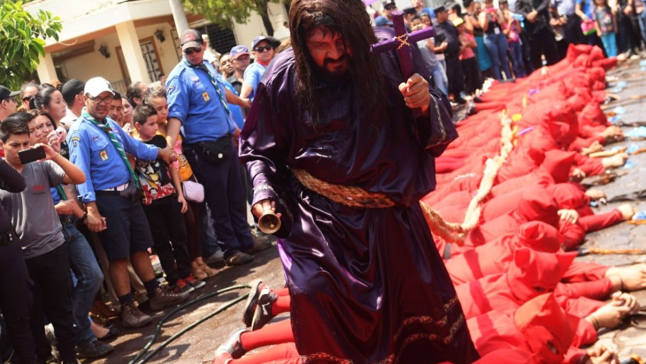 """A faithful fancy dressed as Jesus Christ walks over a lying group of masked """"talciguines"""" --characters of the local folklore-- as part of the celebration of an ancient local tradition that marks the start of Holy Week, on April 10, 2017 in Texistepeque, some 83 km west of San Salvador. The talciguines are devils who lash Catholic faithful to cleanse their sins. / AFP PHOTO / Marvin RECINOS (Photo credit should read MARVIN RECINOS/AFP/Getty Images)"""