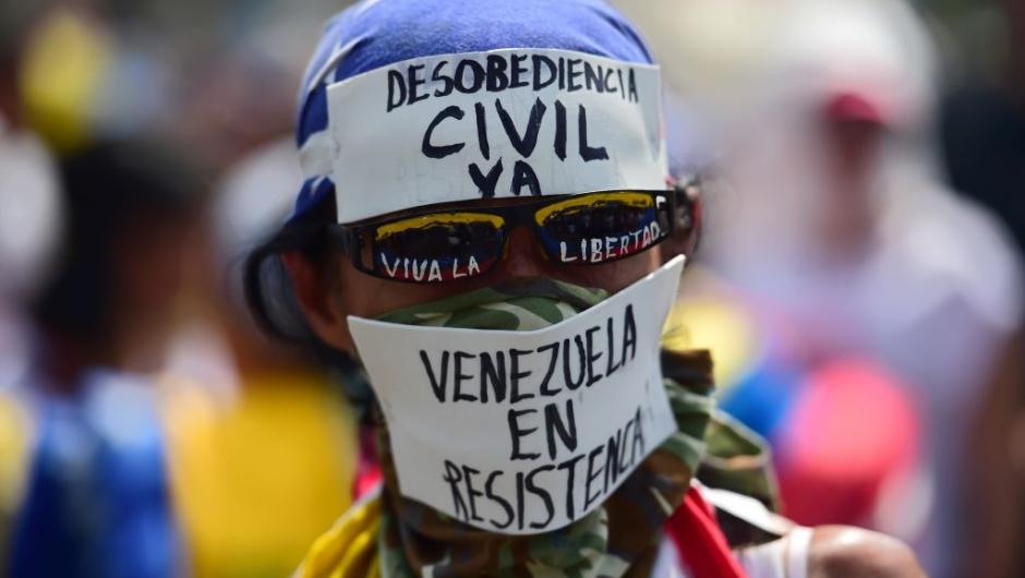 A demonstrator against President Nicolas Maduro's government calls to Civil Disobedience during a protest at the east side of Caracas on April 19, 2017. Venezuela braced for rival demonstrations Wednesday for and against President Nicolas Maduro, whose push to tighten his grip on power has triggered waves of deadly unrest that have escalated the country's political and economic crisis. / AFP PHOTO / RONALDO SCHEMIDT (Photo credit should read RONALDO SCHEMIDT/AFP/Getty Images)