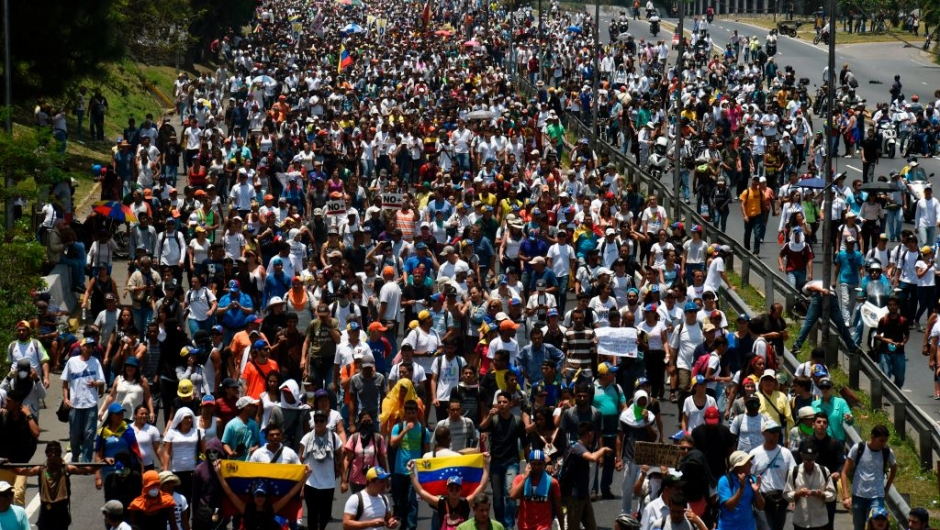 "Opposition demonstrators march in Caracas on April 26, 2017. Protesters in Venezuela plan a high-risk march against President Maduro Wednesday, sparking fears of fresh violence after demonstrations that have left 26 dead in the crisis-wracked country. The placard reads ""Jailed Students and Loose Delinquents"" / AFP PHOTO / JUAN BARRETO (Photo credit should read JUAN BARRETO/AFP/Getty Images)"