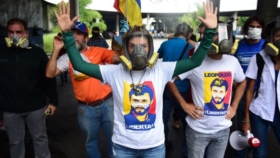 wears a gas mask during clashes with riot police ensueing a protest march in Caracas on April 26, 2017. Protesters in Venezuela plan a high-risk march against President Maduro Wednesday, sparking fears of fresh violence after demonstrations that have left 26 dead in the crisis-wracked country. / AFP PHOTO / RONALDO SCHEMIDT (Photo credit should read RONALDO SCHEMIDT/AFP/Getty Images)