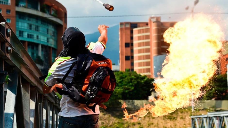 An opposition activist clashes with riot police during a protest march against President Nicolas Maduro in Caracas on April 26, 2017. Venezuelan riot police fired tear gas to stop anti-government protesters from marching on central Caracas, the latest clash in a wave of unrest that, up to now, has left 26 people dead. / AFP PHOTO / RONALDO SCHEMIDT (Photo credit should read RONALDO SCHEMIDT/AFP/Getty Images)