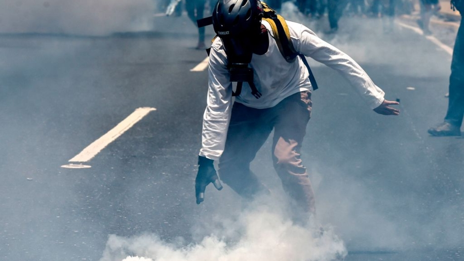 An opposition activist clashes with riot police during a protest against President Nicolas Maduro in Caracas on April 26, 2017. Venezuelan riot police fired tear gas to stop anti-government protesters from marching on central Caracas, the latest clash in a wave of unrest that, up to now, has left 26 people dead. / AFP PHOTO / JUAN BARRETO (Photo credit should read JUAN BARRETO/AFP/Getty Images)