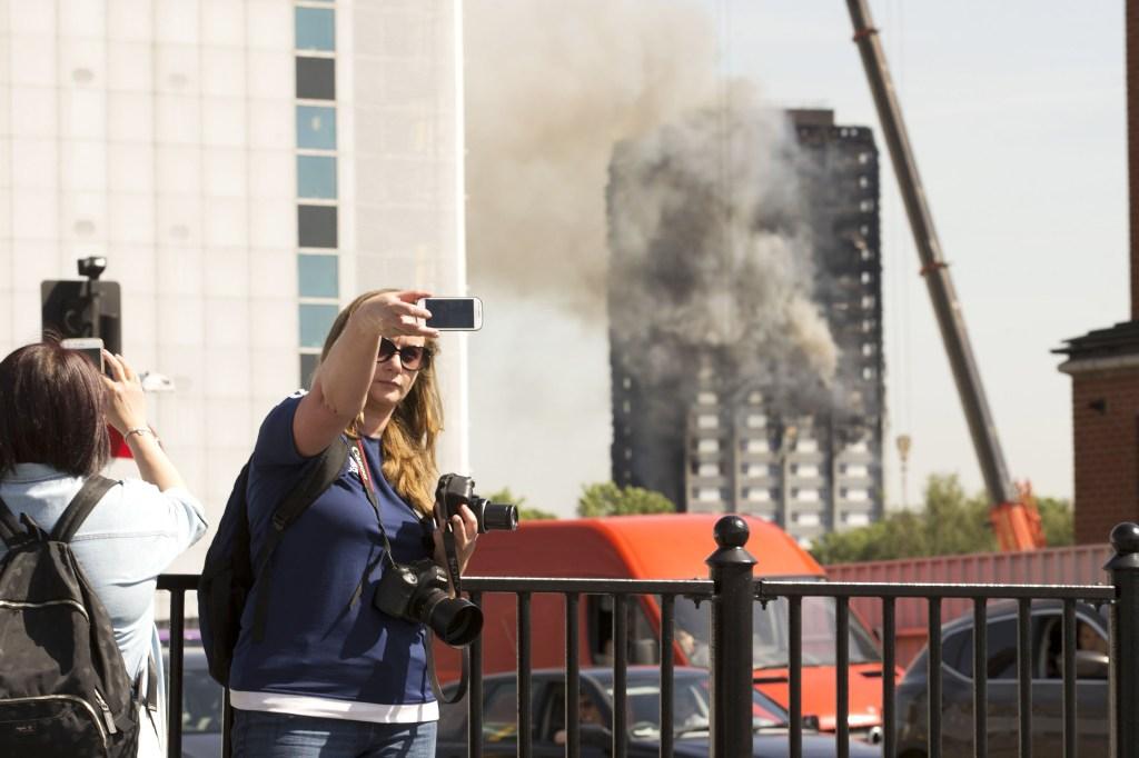 Una mujer toma una 'selfie' con la Torre Grenfell de fondo.