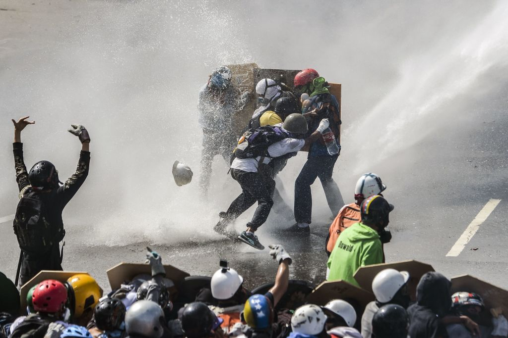 TOPSHOT - Opposition activists are hit by the jet of a riot police water cannon during a protest against President Nicolas Maduro in Caracas, on May 10, 2017. Both the Venezuelan government and the opposition admit that violent protests that have gripped the country for nearly two months are out of control -- and analysts warn they could be a double-edged sword that might trigger even more unrest. / AFP PHOTO / LUIS ROBAYO (Photo credit should read LUIS ROBAYO/AFP/Getty Images)