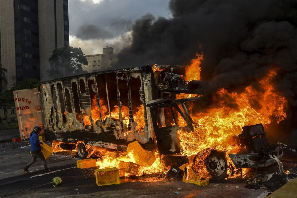 TOPSHOT - Anti-government protesters block the Francisco Fajardo highway in Caracas during a demonstration against Venezuelan President Nicolas Maduro on May 27, 2017. Demonstrations that got underway in late March have claimed the lives of 58 people, as opposition leaders seek to ramp up pressure on Venezuela's leftist president, whose already-low popularity has cratered amid ongoing shortages of food and medicines, among other economic woes. / AFP PHOTO / LUIS ROBAYO (Photo credit should read LUIS ROBAYO/AFP/Getty Images)