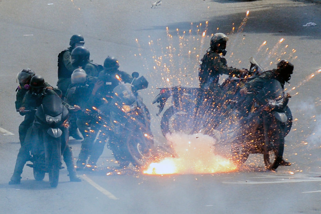 "TOPSHOT - A firework launched by opposition activists explodes amid a group of National Guard riot police motorcyclists during a protest against President Nicolas Maduro's government, in Caracas on May 31, 2017. Venezuelan authorities on Wednesday began signing up candidates for a planned constitutional reform body, a move that has inflamed deadly unrest stemming from anti-government protests. Opponents of socialist President Nicolas Maduro say he aims to keep himself in power by stacking the planned ""constituent assembly"" with his allies. / AFP PHOTO / FEDERICO PARRA (Photo credit should read FEDERICO PARRA/AFP/Getty Images)"