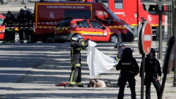 "TOPSHOT - EDITORS NOTE: Graphic content / Rescuers cover with a white sheet the body of a man lying in a sealed off area of the Champs-Elysees avenue in Paris, on June 19, 2017 , after a car crashed into a police van before bursting into flames, with the driver being armed, probe sources said. A car burst into flames after it crashed into a police van on the Champs-Elysees avenue in Paris on June 19, police and investigators said, adding that the driver was armed and it appeared to be a ""deliberate"" act. Authorities said the driver was ""most probably dead"". / AFP PHOTO / Thomas SAMSON (Photo credit should read THOMAS SAMSON/AFP/Getty Images)"