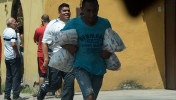 People carry stolen merchandise during lootings in Maracay, Aragua State, Venezuela on June 27, 2017. A political and economic crisis in the oil-producing country has spawned often violent demonstrations by protesters demanding President Nicolas Maduro's resignation and new elections. The unrest has left 76 people dead since April 1. / AFP PHOTO / Federico PARRA (Photo credit should read FEDERICO PARRA/AFP/Getty Images)