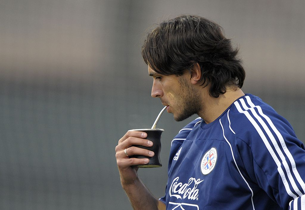 "Paraguay's forward Roque Santa Cruz drinks ""terere"" (typical Paraguayan yerba mate infusion prepared with cold water) during a training session at Michaelhouse School in Balgowan on June 21, 2010, a day after the team's 2-0 win over Slovakia. Paraguay heads to their third 2010 World Cup, Group F, football match against New Zealand on June 24 at Peter Mokaba stadium in Polokwane. AFP PHOTO / JUAN MABROMATA (Photo credit should read JUAN MABROMATA/AFP/Getty Images)"
