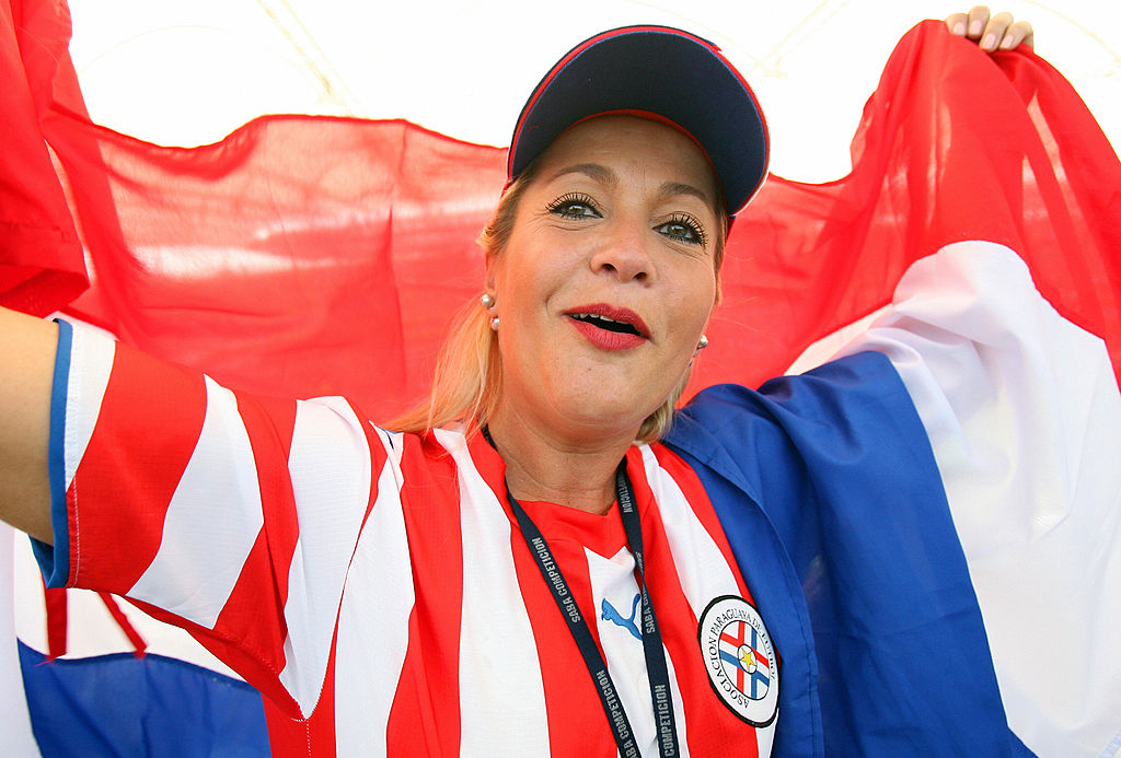Frankfurt am Main, GERMANY: A Paraguay fan cheers while holding the country's flag at Frankfurt's World Cup Stadium ahead of the first round Group B 2006 World Cup football match between England and Paraguay, 10 June 2006. Paraguay are making their third successive World Cup appearance, and their sixth in total, with their best performances coming in 1986, 1998 and 2002 when they reached the last 16. AFP PHOTO / VALERY HACHE (Photo credit should read VALERY HACHE/AFP/Getty Images)