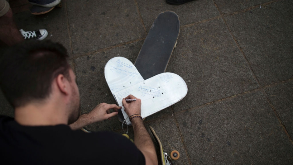 LAS ROZAS, SPAIN - JUNE 08: A skater writes a message on a heart shape skateboard during a vigil in tribute to Ignacio Echavarria, a victim of the London terror attack, outside of Las Rozas City Council on June 8, 2017 in Las Rozas, Madrid province, Spain. Spanish Ignacio Echevarria 39, was confirmed yesterday as one of the 8 victims of London Bridge terror attack. Echevarria is hailed as 'skateboard hero' after he confronted the three terrorists using his skateboard when they were attacking other members of the public with knives near Borough Market in London on June 3. All three terrorists were gunned down by police moments later. (Photo by Pablo Blazquez Dominguez/Getty Images)