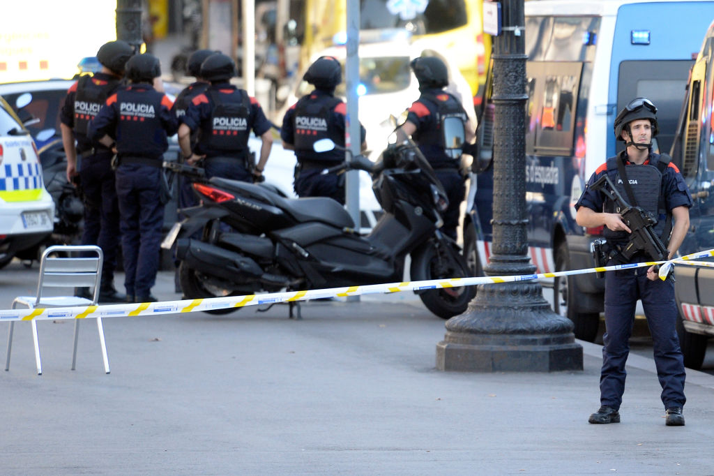 "Armed policemen stand in a cordoned off area after a van ploughed into the crowd, injuring several persons on the Rambla in Barcelona on August 17, 2017. Police in Barcelona said they were dealing with a ""terrorist attack"" after a vehicle ploughed into a crowd of pedestrians on the city's famous Las Ramblas boulevard on August 17, 2017. Police were clearing the area after the incident, which has left a number of people injured. / AFP PHOTO / Josep LAGO (Photo credit should read JOSEP LAGO/AFP/Getty Images)"
