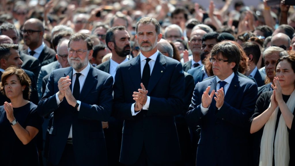Spain's King Felipe VI (C), Spanish Prime Minister Mariano Rajoy (2ndL), President of Catalonia Carles Puigdemont (2ndR), Spanish vice-President of the Government and Minister of the Presidency and of the Regional Administrations Soraya Saenz de Santamaria (L) and Barcelona's mayor Ada Colau applaud after observing a minute of silence for the victims of the Barcelona attack at Plaza de Catalunya on August 18, 2017, a day after a van ploughed into the crowd, killing 13 persons and injuring over 100 on the Rambla in Barcelona. Drivers have ploughed on August 17, 2017 into pedestrians in two quick-succession, separate attacks in Barcelona and another popular Spanish seaside city, leaving 13 people dead and injuring more than 100 others. In the first incident, which was claimed by the Islamic State group, a white van sped into a street packed full of tourists in central Barcelona on Thursday afternoon, knocking people out of the way and killing 13 in a scene of chaos and horror. Some eight hours later in Cambrils, a city 120 kilometres south of Barcelona, an Audi A3 car rammed into pedestrians, injuring six civilians -- one of them critical -- and a police officer, authorities said. / AFP PHOTO / Josep LAGO (Photo credit should read JOSEP LAGO/AFP/Getty Images)