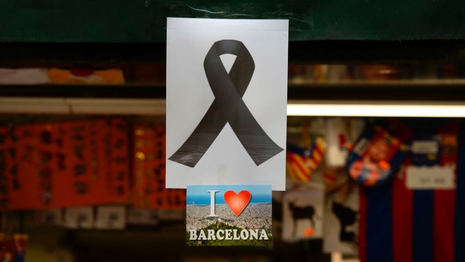"""A picture taken on August 18, 2017 shows a black ribbon stuck above a postcard of Barcelona reading """"I love Barcelona"""" both displayed on the window of a kiosk of the Rambla boulevard, a day after a van ploughed into the crowd, killing 13 persons and injuring over 100 on the Rambla in Barcelona. Drivers have ploughed on August 17, 2017 into pedestrians in two quick-succession, separate attacks in Barcelona and another popular Spanish seaside city, leaving 13 people dead and injuring more than 100 others. In the first incident, which was claimed by the Islamic State group, a white van sped into a street packed full of tourists in central Barcelona on Thursday afternoon, knocking people out of the way and killing 13 in a scene of chaos and horror. Some eight hours later in Cambrils, a city 120 kilometres south of Barcelona, an Audi A3 car rammed into pedestrians, injuring six civilians -- one of them critical -- and a police officer, authorities said. / AFP PHOTO / Josep LAGO (Photo credit should read JOSEP LAGO/AFP/Getty Images)"""
