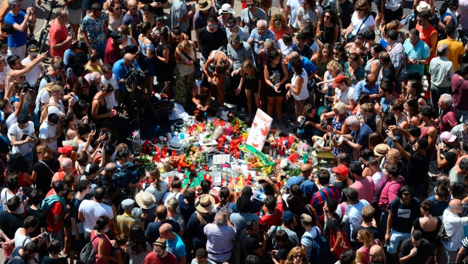 TOPSHOT - People gather to leave candles, flowers, messages, stuffed toys and many differents objects for the victims on August 18, 2017 at the spot where yesterday a van ploughed into the crowd, killing 14 persons and injuring over 100 on the Rambla boulevard in Barcelona. Drivers have ploughed on August 17, 2017 into pedestrians in two quick-succession, separate attacks in Barcelona and another popular Spanish seaside city, leaving 14 people dead and injuring more than 100 others. In the first incident, which was claimed by the Islamic State group, a white van sped into a street packed full of tourists in central Barcelona on Thursday afternoon, knocking people out of the way and killing 13 in a scene of chaos and horror. Some eight hours later in Cambrils, a city 120 kilometres south of Barcelona, an Audi A3 car rammed into pedestrians, injuring six civilians -- one of them critical -- and a police officer, authorities said. / AFP PHOTO / Josep LAGO (Photo credit should read JOSEP LAGO/AFP/Getty Images)