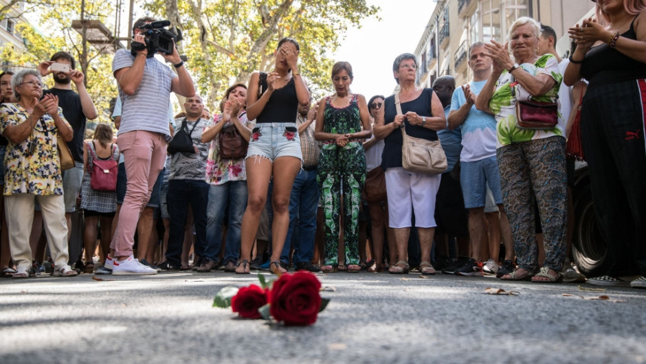 BARCELONA, SPAIN - AUGUST 18: People gather around roses laid on the ground on Las Ramblas after a one minute's silence for the victims of yesterday's terrorist attack, on August 18, 2017 in Barcelona, Spain. Fourteen people were killed and dozens injured when a van hit crowds in the Las Ramblas area of Barcelona on Thursday. Spanish police have also killed five suspected terrorists in the town of Cambrils to stop a second terrorist attack. (Photo by Carl Court/Getty Images)
