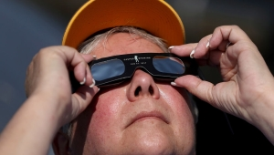 "CASPER, WY - AUGUST 21: A visitor looks at the solar eclipse at South Mike Sedar Park on August 21, 2017 in Casper, Wyoming. Millions of people have flocked to areas of the U.S. that are in the ""path of totality"" in order to experience a total solar eclipse. During the event, the moon will pass in between the sun and the Earth, appearing to block the sun. (Photo by Justin Sullivan/Getty Images)"