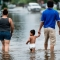 People walk through flooded streets as the effects of Hurricane Henry are seen August 26, 2017 in Galveston, Texas.